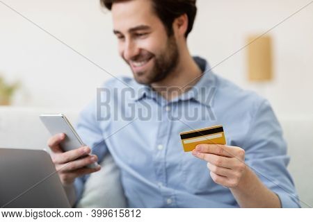 Joyful Guy Shopping Online With Cellphone And Credit Card Sitting On Couch At Home, Focus On Bank Ca