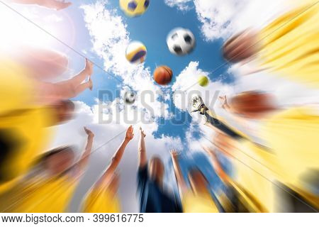 Group Of Happy Sports Team With Coach Throwing Team Sports Balls. Summer Sky With Clouds In The Back