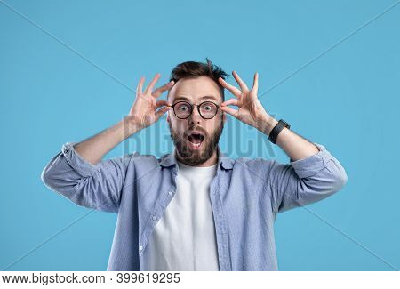 Unbelievable Offer. Amazed Caucasian Guy In Casual Outfit And Glasses Opening Mouth In Surprise On B