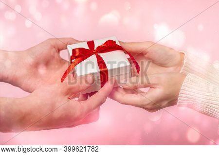 Man And Woman Hands Holding Gift Box With Red Bow On Pink Glow Bokeh Background, Close-up. Pastel Co