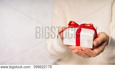 Beauty Woman Hands Holding Gift Box With Red Bow On White Background, Close-up. Pastel Colors, Copy
