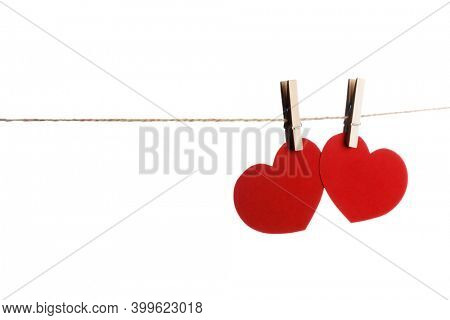 Clothes pegs and two red paper hearts on rope isolated on white background Valentines day concept
