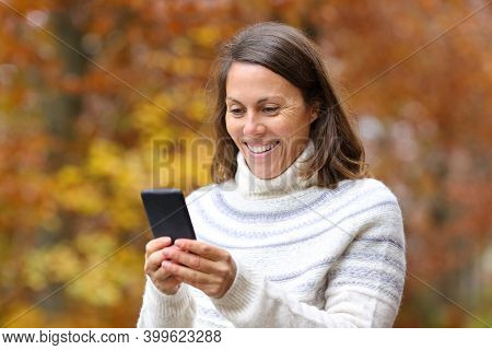 Happy Middle Age Woman Using Smart Phone Walking In Fall Season In A Park