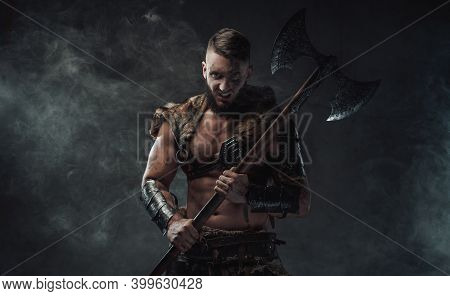 Brutal Nordic Heathen Dressed In Light Armour Posing In Dark Smokey Background With Huge Axe And Sta