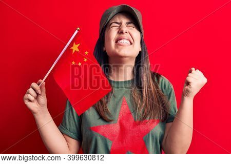 Beautiful patriotic woman wearing t-shirt with red star communist symbol holding china flag screaming proud, celebrating victory and success very excited with raised arm