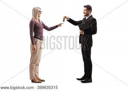 Salesman giving car keys to a young blond woman isolated on white background