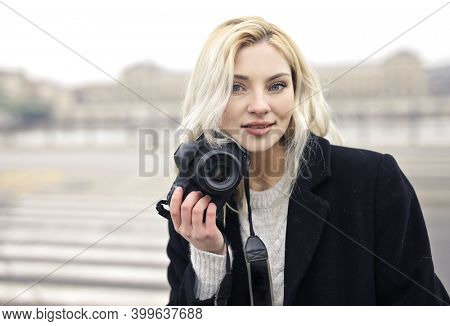 portrait of young woman with digital camera
