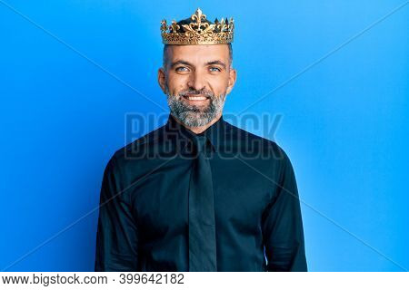 Middle age handsome business man wearing king crown looking positive and happy standing and smiling with a confident smile showing teeth