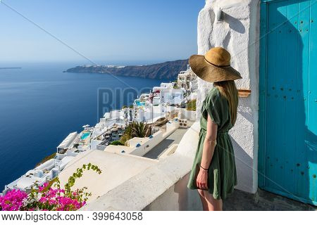 Santorini Greece, September 17, 2020: Young Woman In A Hat Looks At The Sea In Imerovigli Village On