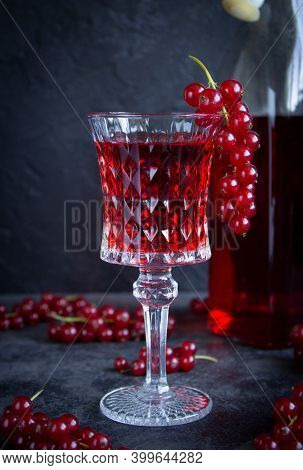Red Currant Drink In A Glass Goblet On A Gray Cement Surface. A Bunch Of Red Currants On A Glass Nd