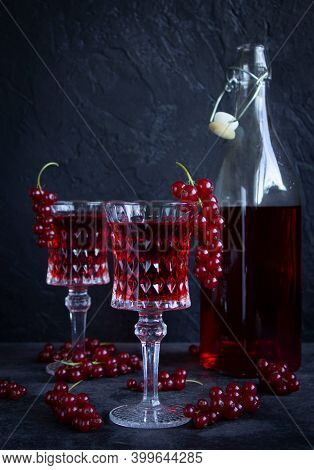 Two Glass Goblets With Red Currant Drink On A Gray Cement Surface. A Bunch Of Red Currants On A Glas