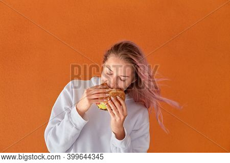 A Young Woman With Pink Hair Eats Delicious Food. Big Burger. Orange Background.