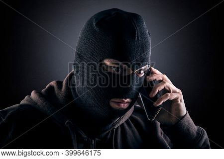 Criminal wearing black balaclava and hoodie with a smartphone in the dark