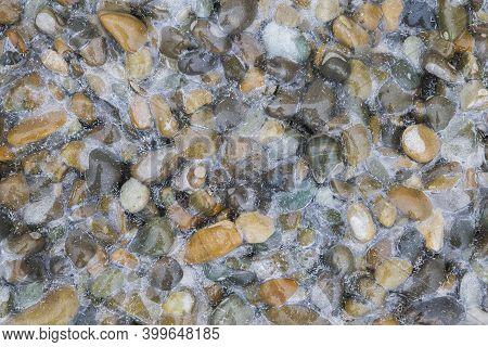 Frozen Multicolored Round Cobblestones On The Seashore
