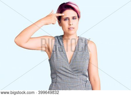 Young beautiful woman with pink hair wearing casual clothes pointing unhappy to pimple on forehead, ugly infection of blackhead. acne and skin problem