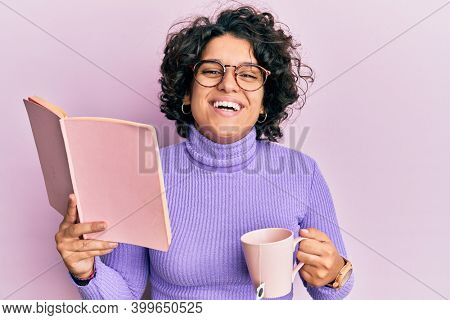 Young hispanic woman with curly hair reading a book and drinking a cup of coffee smiling and laughing hard out loud because funny crazy joke.