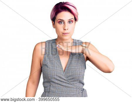 Young beautiful woman with pink hair wearing casual clothes cutting throat with hand as knife, threaten aggression with furious violence