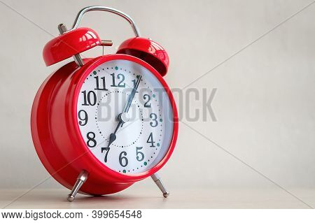 Close-up And Selective Focus Of Red Metal Retro Alarm Clock That Show Seven O'clock. Concept Of Morn