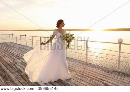 Gorgeous Bride In Beautiful Wedding Dress With Bouquet Near River On Sunset