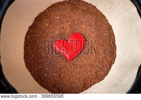 Close-up Of A Red Heart Lying On The Ground Coffee In A Special Craft Bag In The Coffee Maker. The C