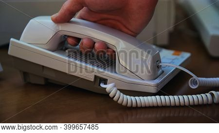 A Hand Of A Man Picking Up The Receiver Of A Vintage Retro Telephone And Answering The Call. Media.