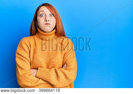 Beautiful redhead woman with arms crossed gesture puffing cheeks with funny face. mouth inflated with air, catching air.