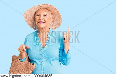 Senior beautiful woman with blue eyes and grey hair wearing fashion dress and hat holding summer wicker handbag surprised with an idea or question pointing finger with happy face, number one