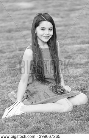 Salon Haircare You Will Love. Little Child Sit On Green Grass. Small Girl With Long Brunette Hair. H