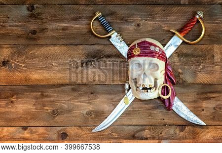 Jolly Pirate Scull In Bandanna With Crossed Swords And Golden Teeth On Wooden Background. Dead Bone