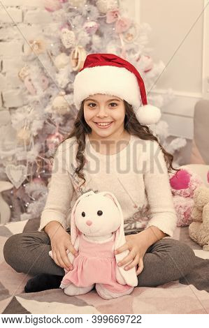Waiting For Santa. Small Girl In Santa Hat Cuddle Soft Toy. Happy Child Celebrate Xmas And New Year.