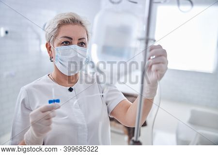 Medicine Worker In Mask Preparing An Intravenous Vitamin Drip Treatment In Beauty Clinic