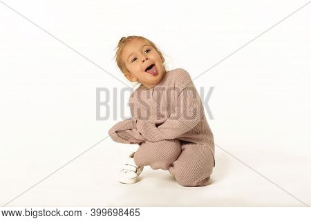 Cute Little Blond Baby Girl Sit The Floor In Pink Knitted Pant Suit Show Tongue Full Body Photo