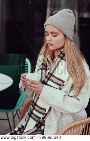 Blond Lgirl In Knitted Hat And Scarf With Cup Of Tea Close Up Portrait In Cafe