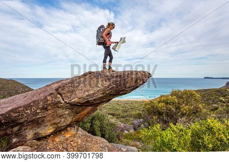 Female Hiker Stands On A Rock With Coastal Views, She Is Carrying A Backpack And Holding A Map