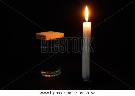 Burning Candle, A Glass With Water And Breads