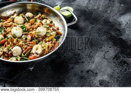 Stir Fry Noodles With Cuttlefish And Vegetables In A Wok Pan. Black Background. Top View. Copy Space