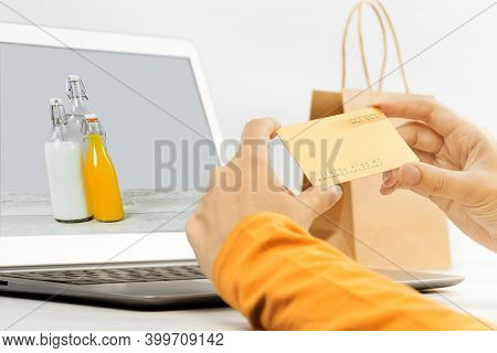 Woman Shopping For Food Online Holding A Gold Credit Card In Hands. E-commerce And Seasonal Sale, Sh