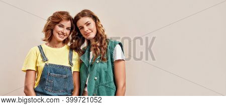 Portrait Of Two Attractive Young Girls, Twin Sisters In Casual Wear Smiling At Camera, Posing Togeth