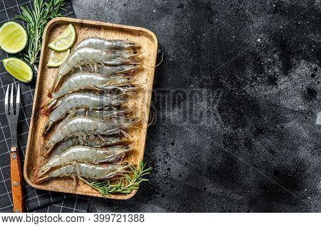 Whole Fresh Raw Langoustine Prawns, Shrimps On A Wooden Tray. Black Background. Top View. Copy Space