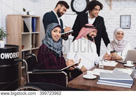 Disabled Arab Woman In Wheelchair Working In Office. Woman Is Sharing Notes With Coworkers.