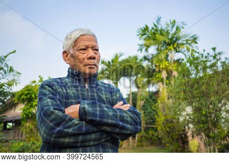 Portrait Of Elderly Asian Man Arms Crossed Standing And Looking Away While Standing In A Garden. Spa