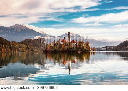Church Of Assumption In Lake Bled, Slovenia With Blue Sky And Clouds In The Autumn