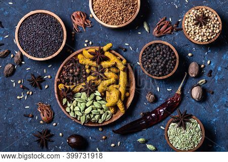 Dry Whole Warming Indian Spices In Wooden Bowls On Dark Blue Concrete Background. Exotic Vitamin, Fl