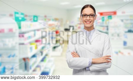 medicine, profession and healthcare concept - happy smiling female pharmacist or doctor in glasses and white coat over pharmacy on background