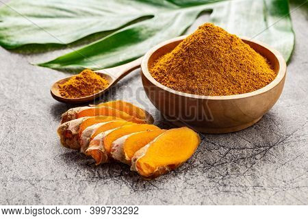 Turmeric Powder And Fresh Slices Of Turmeric Root On Grey Concrete Background. Spice, Natural Colori