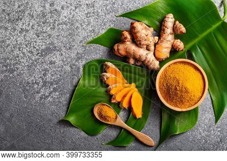 Turmeric Powder And Fresh Turmeric Root On Grey Concrete Background With Copyspace. Spice, Natural C