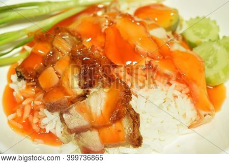 Crispy And Roasted Pork Slice Topping On Plain Rice Dressing Sweet Red Gravy Sauce On Plate