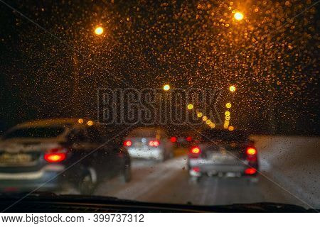 Cars In Traffic In Winter In The Evening Dark Or At Night. View Through The Windshield, Covered With