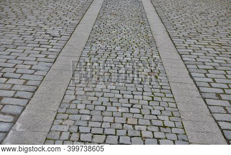 Paving The Street From Gray Granite Cubes. Two Track Lanes Of Other Larger Tiles Symbolize A Train T