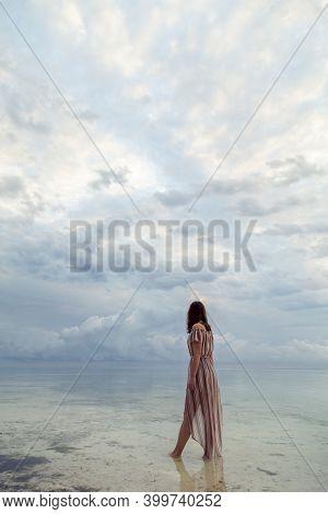 Beautiful Young Woman Walking Down Secluded Beach At Dawn, Enjoying Beautiful Sunrise On Over Indian
